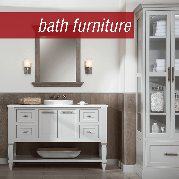 Tall linen cabinet with glass on three sides next to a matching vanity with open shelf on the bottom, decorative legs, and inset doors all in a light grey finish. Part of the Dura Supreme custom bathroom furniture program.