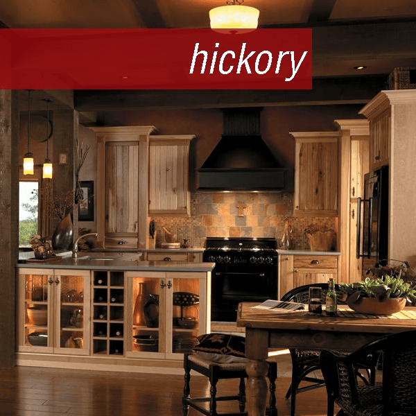 Small open kitchen with glass doors, wine cubes, and breakfast bar in Medallion Cabinetry. Yukon hickory Natural; Rushmore knotty alder Carriage Black Burnt Sienna Glaze  Highlight with Heirloom Distressing; mantel is cherry Carriage Black Burnt Sienna Highlight with Heirloom Distressing