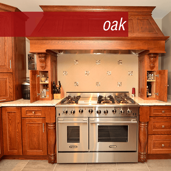 Large Oak kitchen with mantle hood, spice pullout, medium stain, tons of accessories, and decorative turned legs.