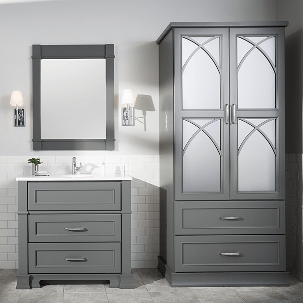 Medium toned grey painted vanity with three large drawers cut out for plumbing and coordinating large double door linen cabinet.